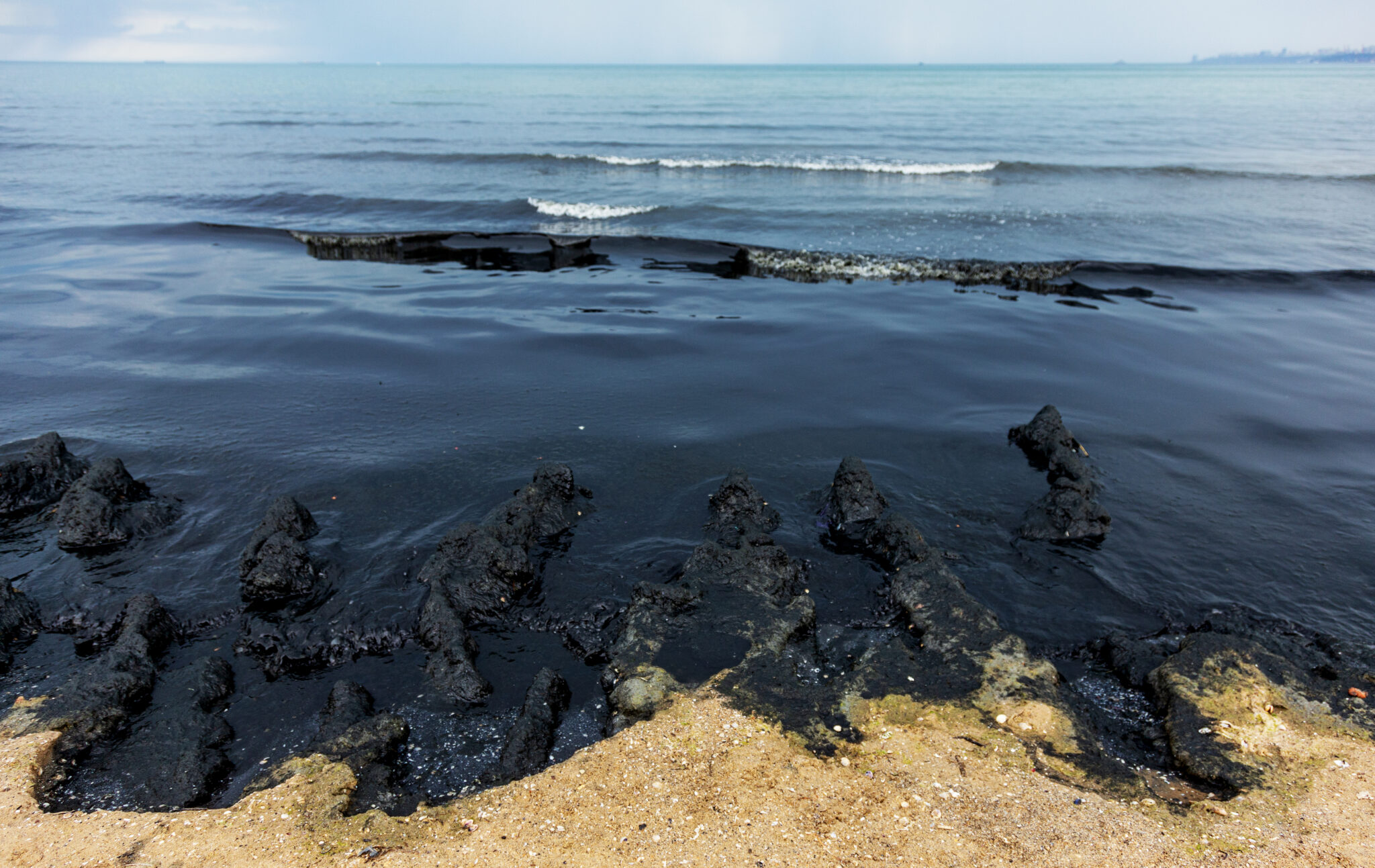 the sea and sand polluted with crude oil