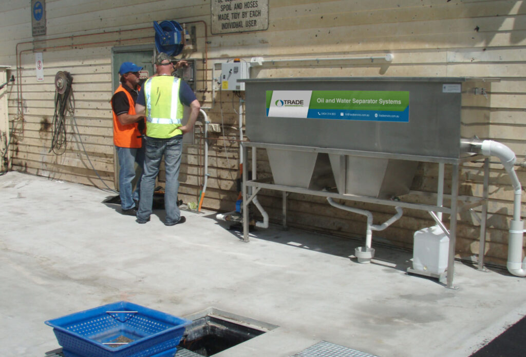 Professionals examine the oil water separator